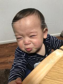 木製のテーブルに座っている小さな子供の写真・画像素材[1802030]