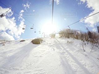 雪の上に空気を通って飛んで男覆われた斜面の写真・画像素材[1836803]