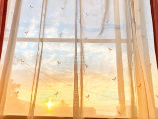レースのカーテン越しの夕焼けの写真・画像素材[2200127]