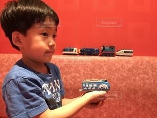 青いTシャツの男の子と赤い壁の写真・画像素材[2257622]