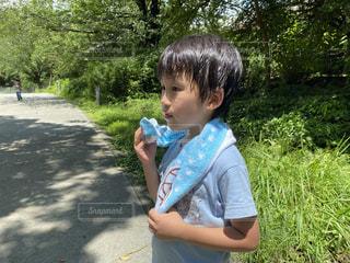 緑の木々とタオルを持った男の子の写真・画像素材[3487063]