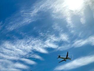 大空に浮かぶ太陽と雲と飛行機の写真・画像素材[2077081]