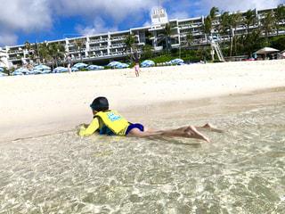沖縄の海にて。波打ち際で寝そべる男の子。の写真・画像素材[2354993]