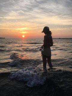 背景に夕日がある浜辺に立っている人の写真・画像素材[2179470]