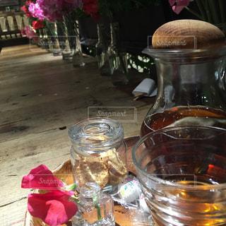 ワインのガラスの横のテーブルの上に花の花瓶の写真・画像素材[1814178]