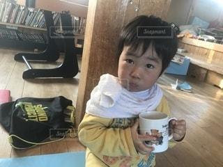 一杯のコーヒーをテーブルに座って若い男の子の写真・画像素材[1787063]