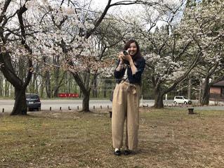 桜の木の前に立っている人の写真・画像素材[1845997]