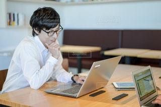 コンピュータを使ってテーブルに座っている人の写真・画像素材[2404684]