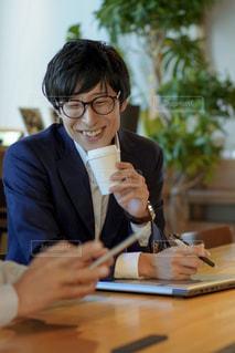 テーブルに座っている男性の写真・画像素材[2404702]