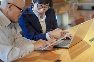 ラップトップを使ってテーブルに座っている人々のグループの写真・画像素材[2405398]