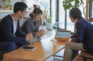 ノートパソコンを見てテーブルに座っている人々のグループの写真・画像素材[2405428]