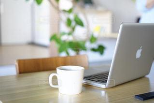 コーヒー1杯とテーブルの上に座るノートパソコンの写真・画像素材[2447513]