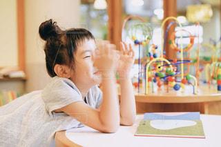 テーブルに座っている小さな女の子の写真・画像素材[2498577]