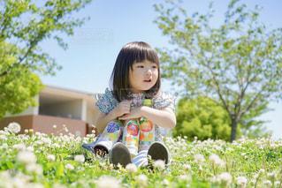 草の上に立っている小さな女の子の写真・画像素材[2220135]