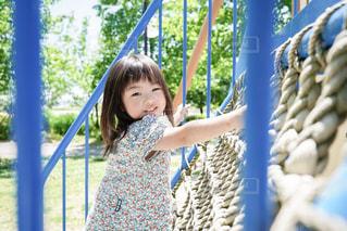 フェンスの前に立っている小さな女の子の写真・画像素材[2232846]