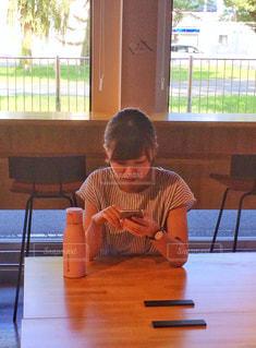 窓の前のテーブルに座っている少年の写真・画像素材[2403173]