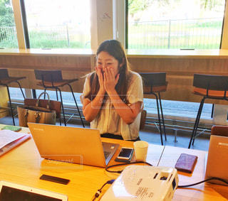 窓の前の机に座っている人の写真・画像素材[2403179]