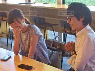 テーブルに座って談笑する男女の写真・画像素材[2403237]