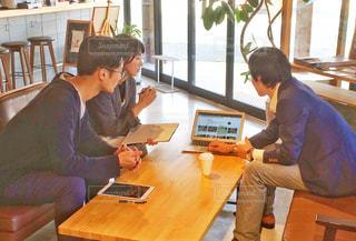 ラップトップコンピュータを使ってテーブルに座っている人々のグループの写真・画像素材[2403335]
