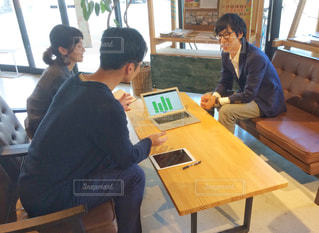 ノートパソコンを持って打ち合わせ中の男女3人組の写真・画像素材[2403453]