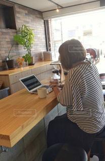 カフェのカウンターに座って、コーヒーを飲みながらパソコンを操作している人の写真・画像素材[2403476]