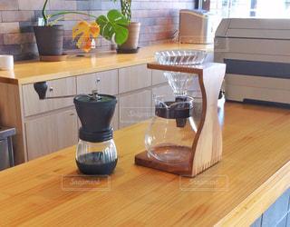 白木のカウンターの上のコーヒーポットの写真・画像素材[2403489]