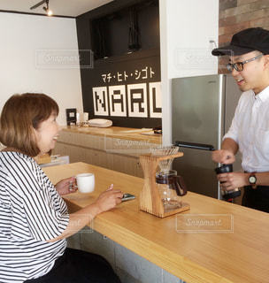 テーブルに座っている男女の写真・画像素材[2403755]