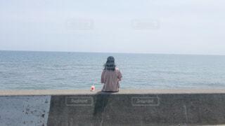 水の体の隣に立っている男の写真・画像素材[4595450]