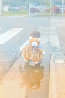 子ども,1人,カバン,屋外,晴れ,後ろ姿,散歩,一人,水たまり,水面,日常,子供,女の子,遊ぶ,人物,背中,外,人,後姿,ひとり,横断歩道,日本,遊び,熊,お散歩,テディベア,1歳,リュック,うしろ姿,子育て,育児,クマ
