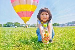 野原に座っている小さな女の子の写真・画像素材[2215554]
