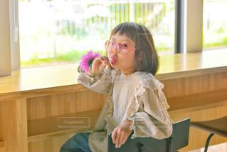 窓の前に座っている小さな女の子の写真・画像素材[2264166]