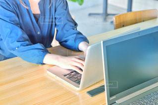 ラップトップコンピュータを使ってテーブルに座っている人の写真・画像素材[2310109]