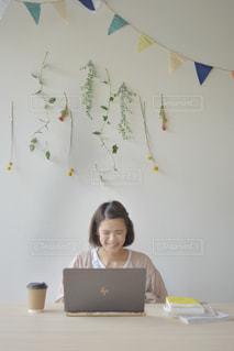 ラップトップを使用してテーブルに座っている人の写真・画像素材[2310220]
