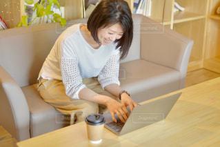 ノートパソコンを使ってソファに座っている女性の写真・画像素材[2312354]