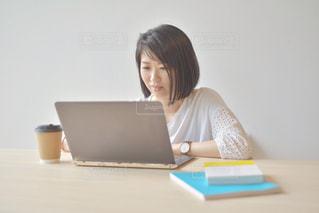 ノートパソコンを使って座っている女性の写真・画像素材[2312424]