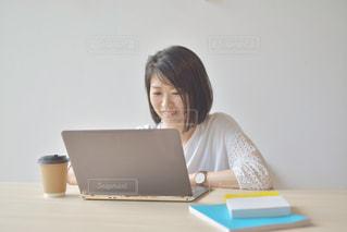 ノートパソコンを使って座っている女性の写真・画像素材[2312425]