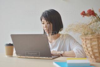 ノートパソコンを使って座っている女性の写真・画像素材[2312426]