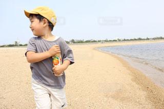 海辺でジュースを持っている男の子の写真・画像素材[2235545]