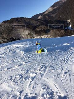 雪に覆われた山をスノーボードに乗ってる女性の写真・画像素材[2943881]