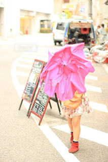 ピンクの傘を持って通りを歩いている人の写真・画像素材[2183745]