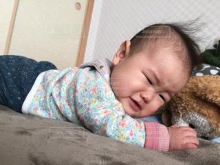 赤ちゃんが布団の上で寝転がっていますの写真・画像素材[1819307]