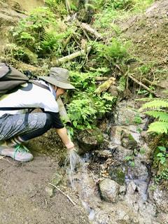 山中の川で手を洗う男性の写真・画像素材[2215541]