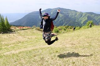 山の上でジャンプする女性の写真・画像素材[2215663]