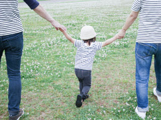 父と母に手を繋がれた女の子の後ろ姿の写真・画像素材[2278285]