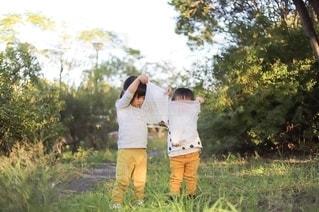草むらで袋を持ち上げる子どもの写真・画像素材[2779933]