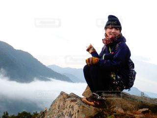 岩の上に座っている女性の写真・画像素材[3575584]