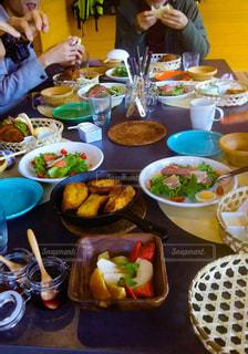 食べ物を食べるテーブルに座っている人々のグループの写真・画像素材[2367121]