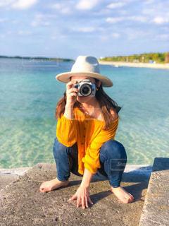 水の体の近くのビーチに座っている人の写真・画像素材[1837582]