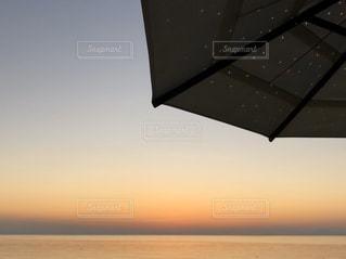 パラソルの下、沈む夕日の写真・画像素材[3003566]