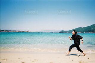 浜辺でフリスビーを投げる男の写真・画像素材[2107649]